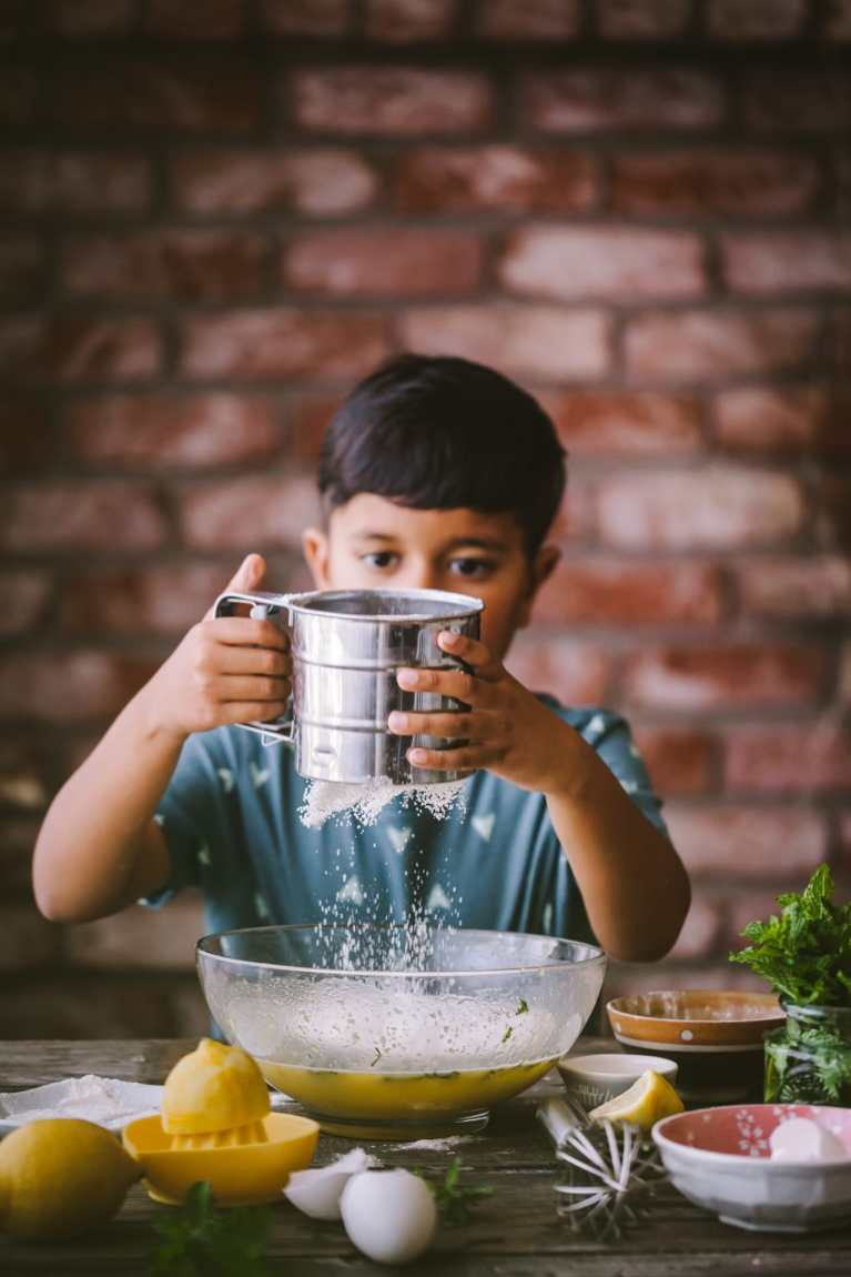Little boy sifting flour to the cake mixing bowl