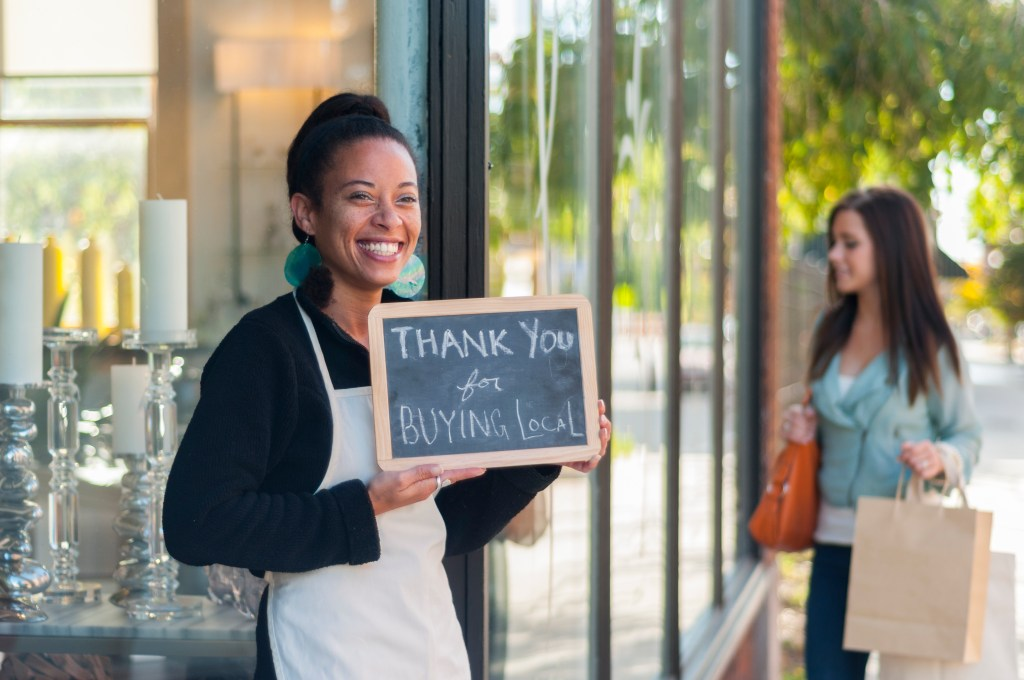 "African-American business owner holding a ""Thank You for Buying Local"" sign in front of her store with shopper in the background."