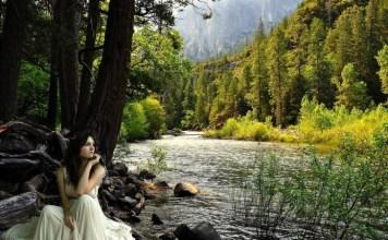Mulher sentada na beira do lago