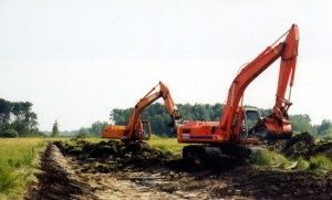 Modern trackhoe creating drainage. Photo Credit: Orlando Hiebert