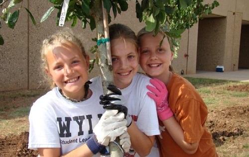 3 girls hug tree they planted at school Copy