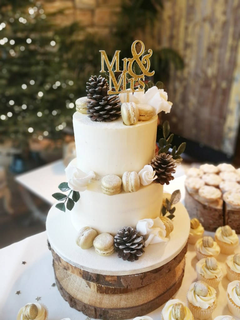 White buttercream winter themed cake, with pine cones and gold macarons