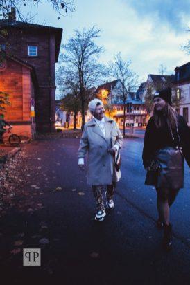 Ursula trägt zur Leoprint-Hose Sneakers und Trenchcoat