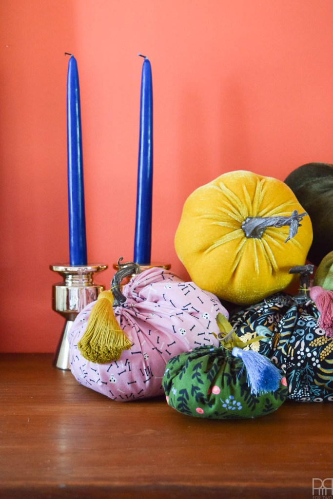 colourful fabric pumpkins against orange wall with blue candles
