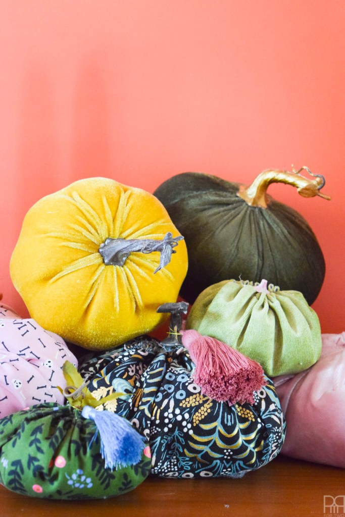detail shot of colourful fabric pumpkins with tassels, against orange wall
