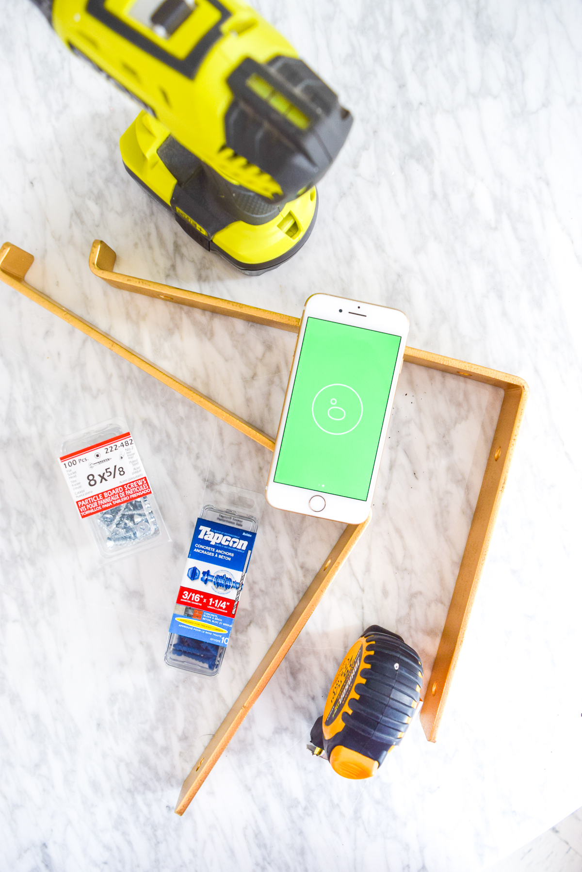 gold shelf bracket and tools on a marble table