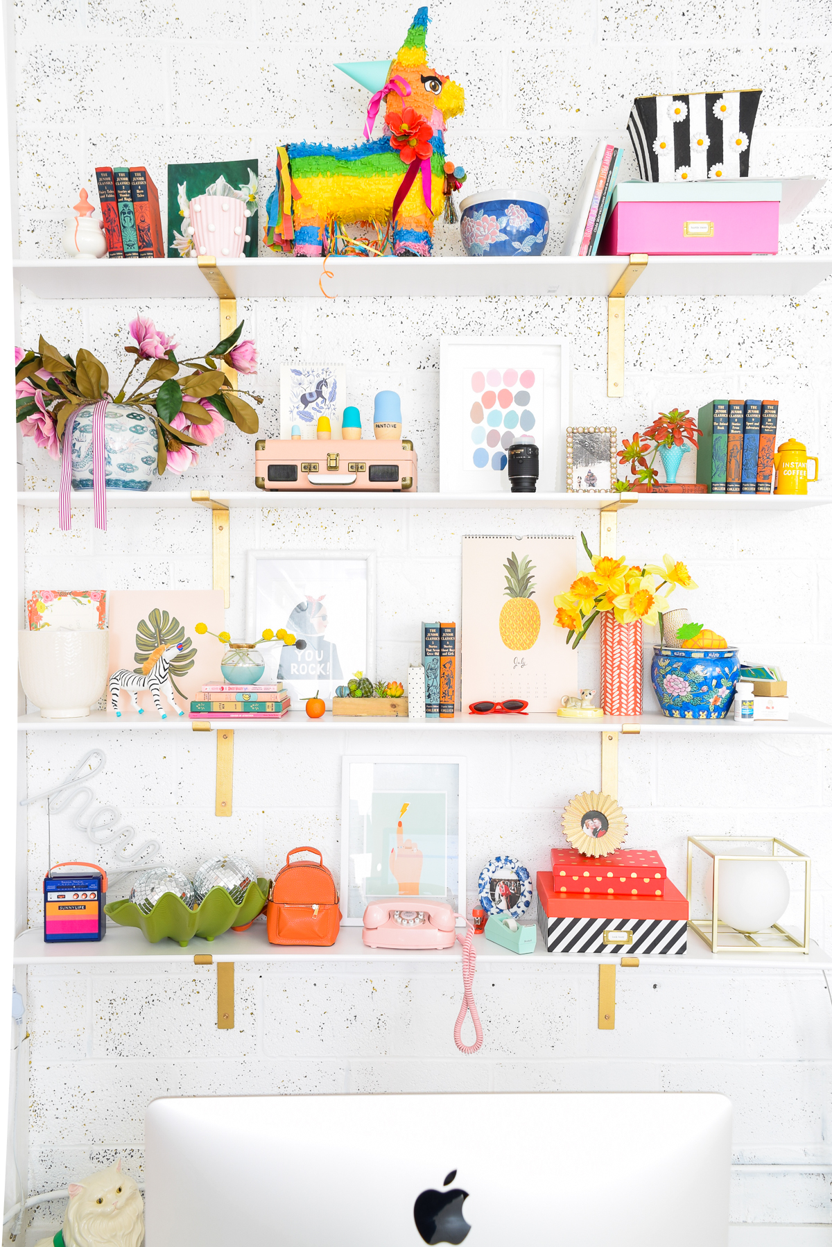 colourfully decorated shelves behind a mac desktop