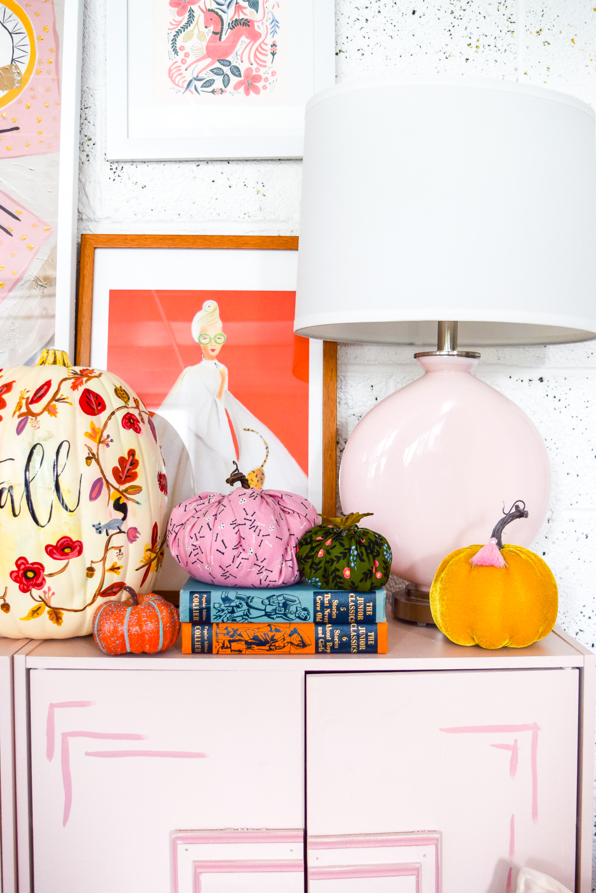 pumpkins and books on a pink dresser