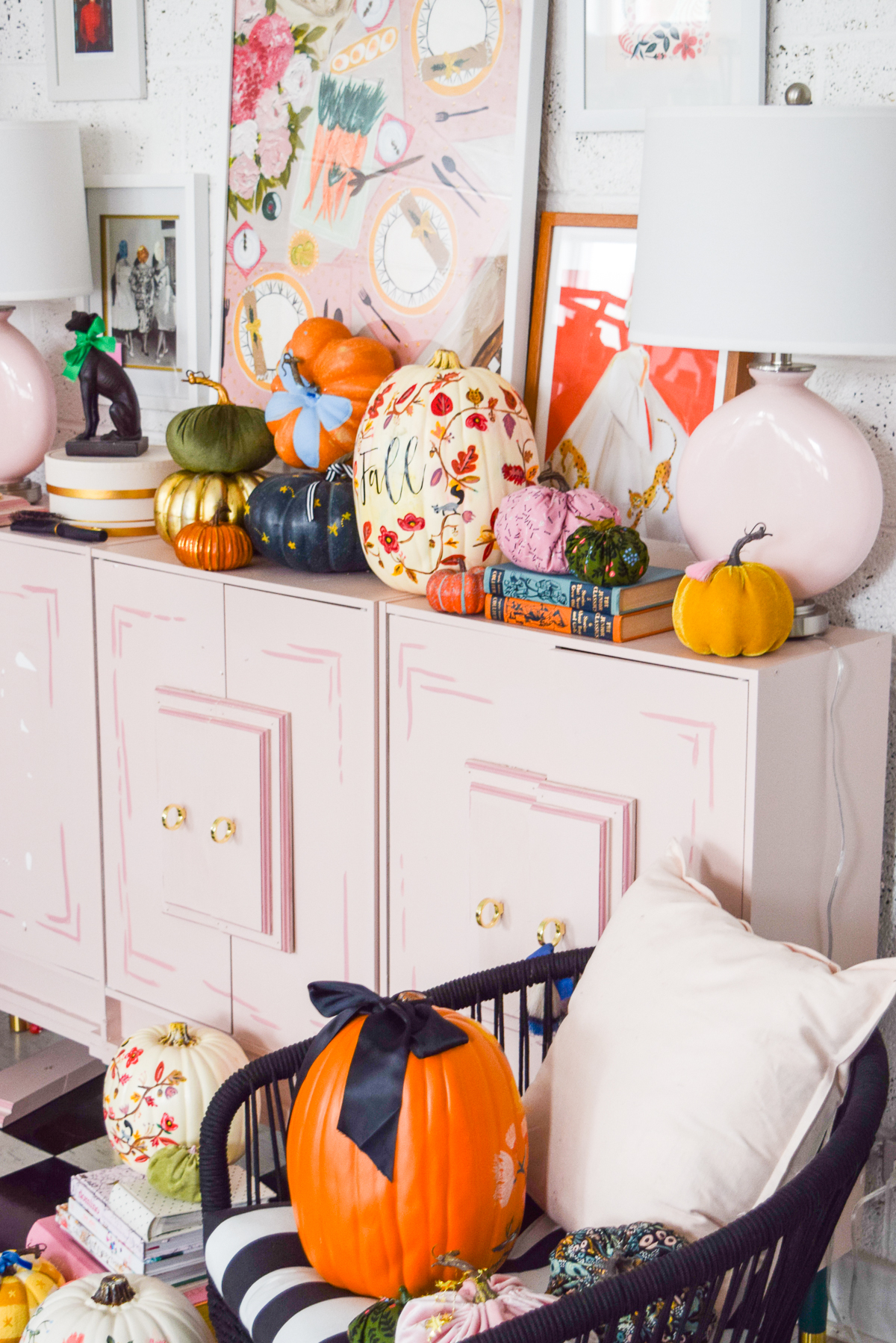 angled shot of a pink dresser with various pumpkins