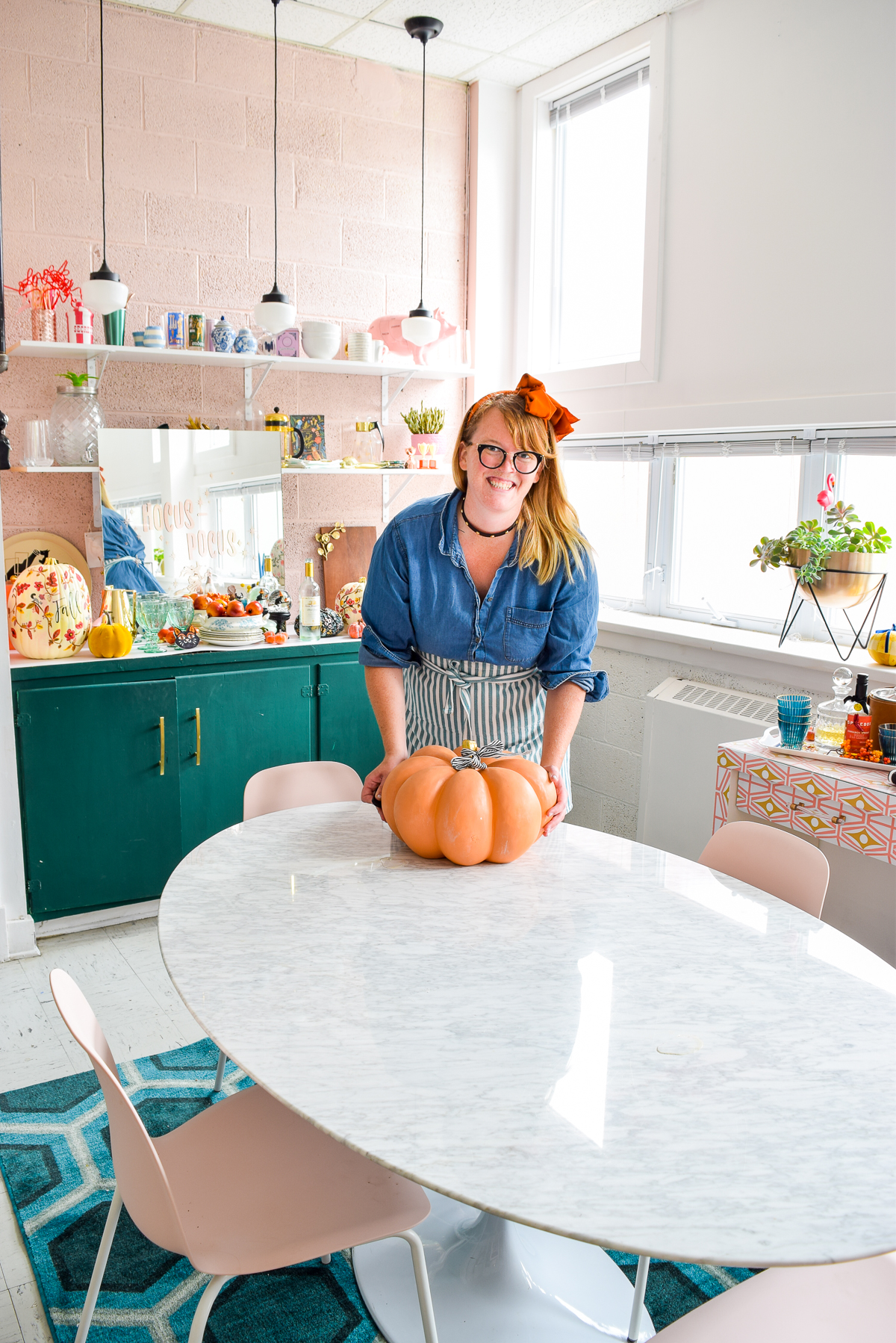 woman putting an orange pumpkin on a marble table