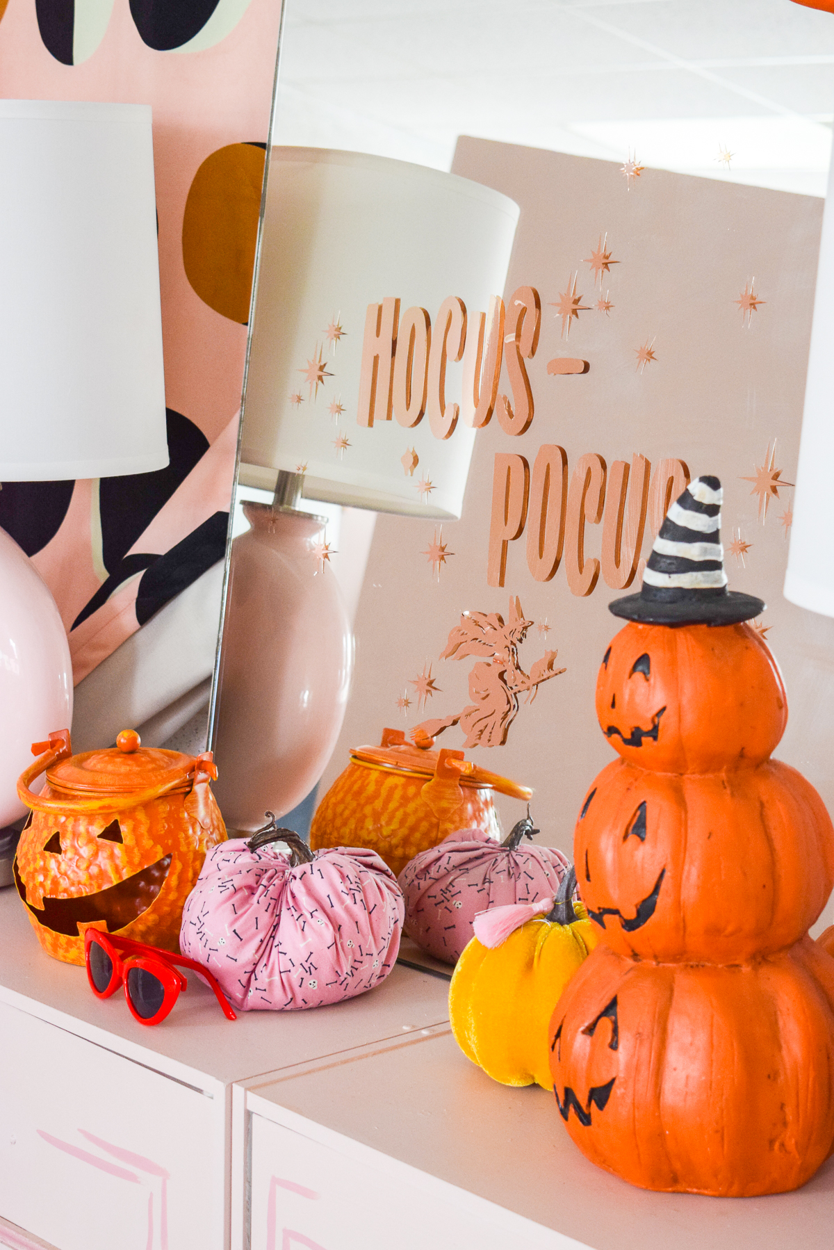 hocus pocus mirror sitting on a pink console with halloween pumpkins