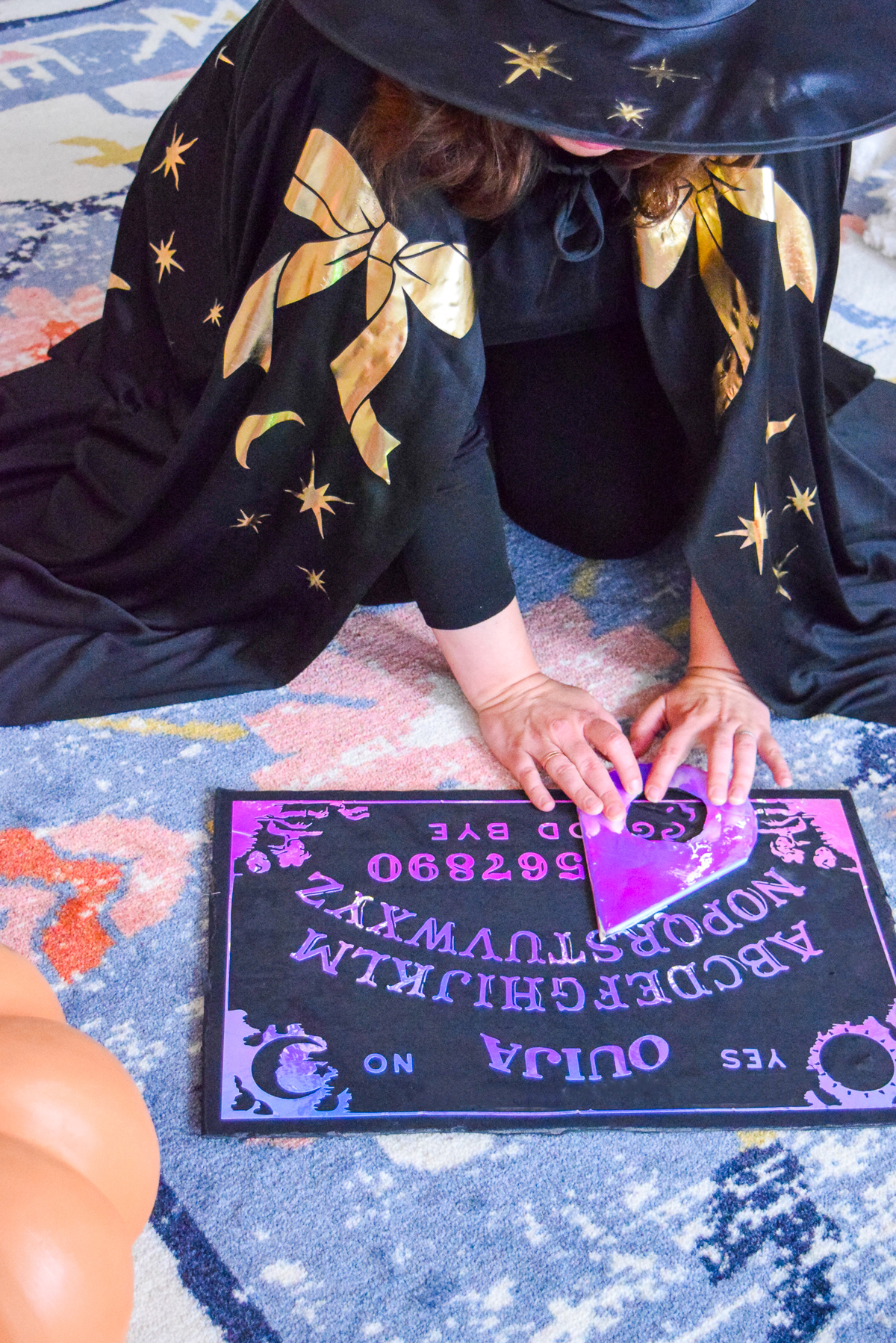 woman in a witch cape moving a planchette on a holographic ouija board