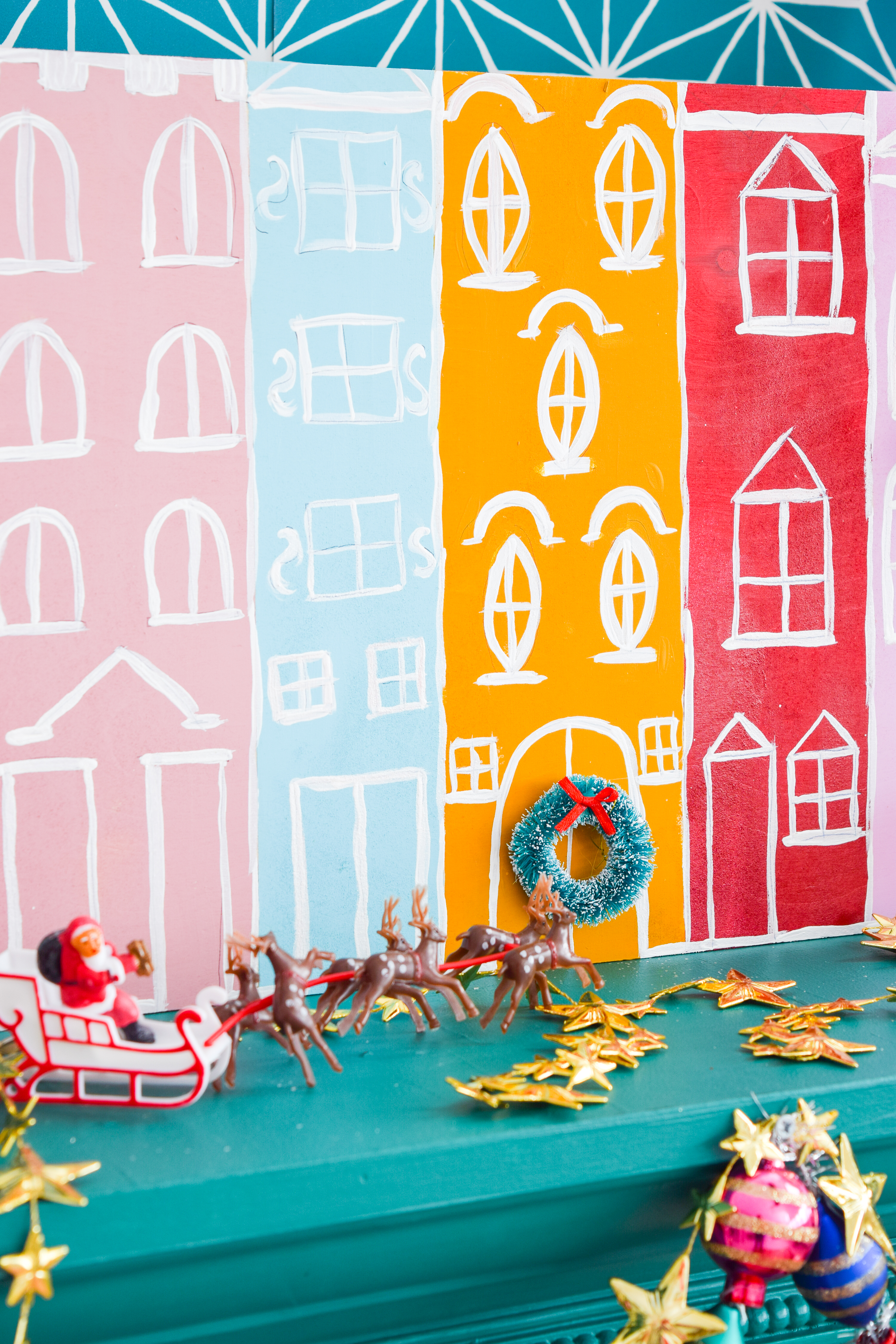 A painted Christmas village is all you need to bring a dose of seasonal cheer (and colour!) to your Christmas mantel, sideboard, or console table! Grab your Americana Acrylic Paints & Dazzling Metallics to get started. #christmascraft #christmasvillage