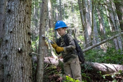 A first-year Ranger uses a handsaw to remove an overhanging limb.