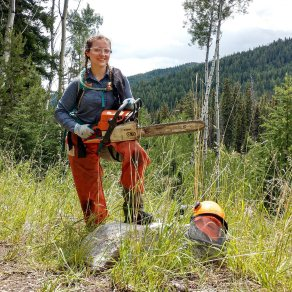 Assistant crew leader, Carly Tryon poses with a chainsaw in the Loomis State Forest. In Wilderness, only hand tools can be legally used to maintain trails. Photo by Sean Miller.