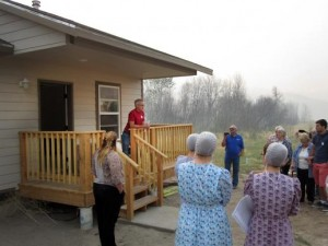 Kevin Froese, on deck at left, of Mennonite Disaster Service, speaks during the Aug. 23 dedication of the first of 11 houses to be completed by ecumenical volunteers after last year's Carlton Complex Fire in Washington. The house was framed by the Amish from Montana, the MDS and United Methodists finished the interior. Photo by Jim Truitt.