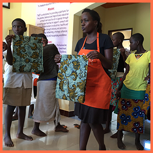 A representative from Days for Girls gives instructions using materials to create products for feminine hygiene. Improving health and education for young women in Uganda has a positive impact on school attendance and overall well-being.