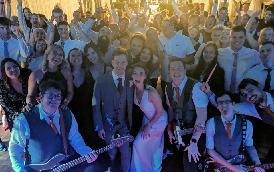 Hampshire Wedding Band The Pocket Rockers provide Live Entertainment for a Wedding at Balmer Lawn Hotel. The entire wedding party is gathered on the dancefloor for a photo with the band.