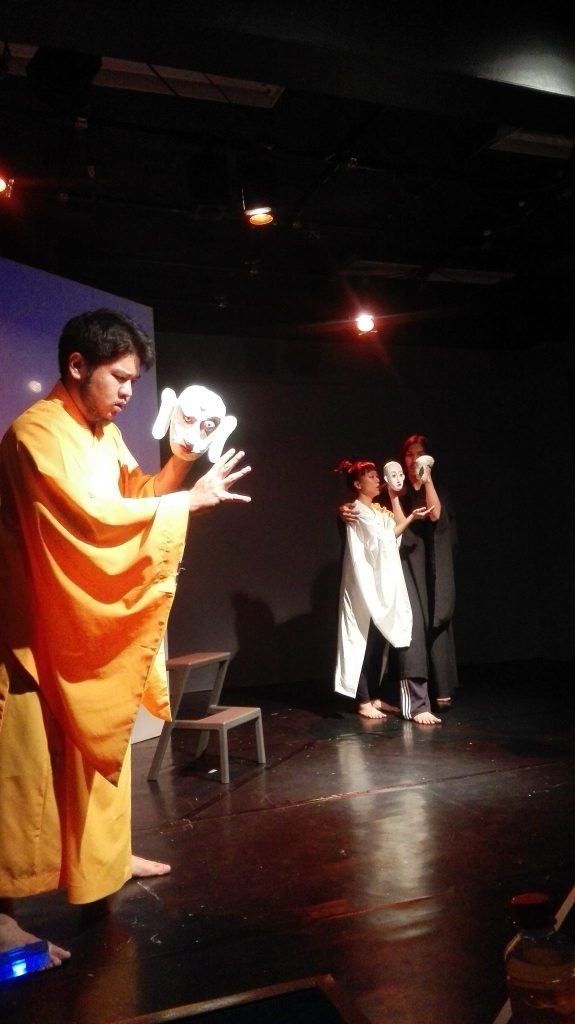 monk looks at the audience in white snake puppet show