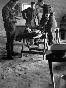 Personnel of the Royal Canadian Army Medical Corps checking the condition of a wounded Canadian soldier being evacuated to a Field Surgical Unit. / Le personnel du Corps de santé royal canadien examine un soldat canadien blessé que l'on transporte à une U Par BiblioArchives / LibraryArchives