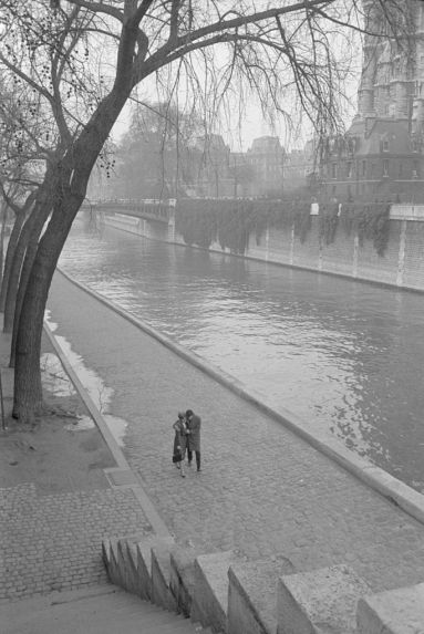 A couple walking along the Seine River in Paris