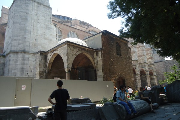 Tourists sitting on remnants of the second church Hagia Sophia
