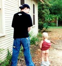 Man peeing outside with a baby copying him