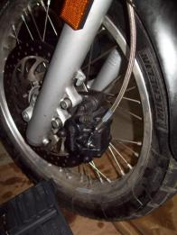 In order to get the front wheel off you want to first take the front brake off. This is done by taking off the two 8mm allens on the left fork. The caliper will just slide right off. Hang out out of the way off of the turn signal for the rest of the project.
