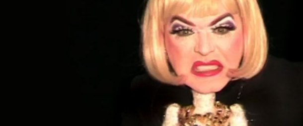 Clementine the Living Fashion Doll is pulling a disgusted face against a black backdrop.