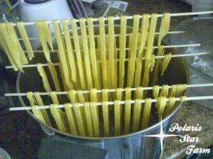 Drying fettucine on bamboo skewers set across a pot.