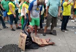 Manifestantes da Avenida Paulista vestem mendigo com os dizeres 'era empresário, virei mendigo'