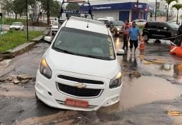 Táxi cai em buraco aberto no asfalto em rotatória que liga Geisel e José Américo