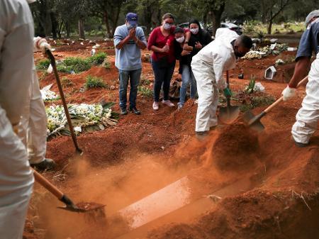 parentes assistem a coveiros vestindo roupas de protecao enterrando o caixao de um homem que morreu da doenca por coronavirus covid 19 no cemiterio de vila formosa 1589423364799 v2 450x337 - Brasil se torna o terceiro país com mais casos confirmados de coronavírus no mundo