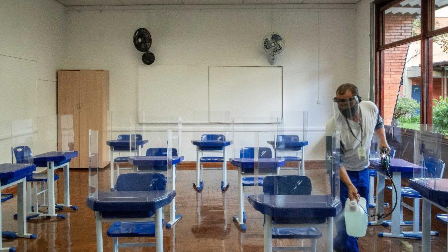 funcionario faz higienizacao de sala de aula de escola particular de sao paulo medida faz parte do protocolo sanitario contra o coronavirus 1611940941958 v2 900x506 - Volta às aulas vira disputa entre professores, escolas e governos