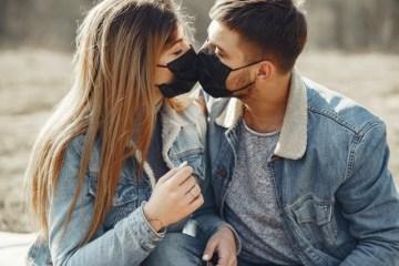 loving young couple kissing while wearing black medical 4005101 - Dia do Beijo: Aplicativo aponta mudanças nos relacionamentos pós-pandemia