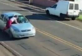 Homem acelera carro com mulher em cima do capô e foge deixando vítima na pista
