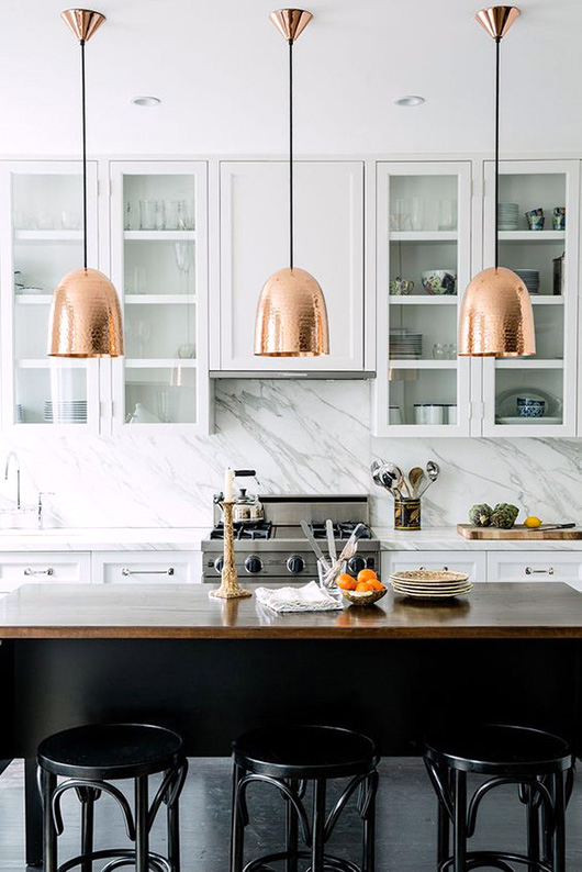 white marble kitchen with copper light fixtures