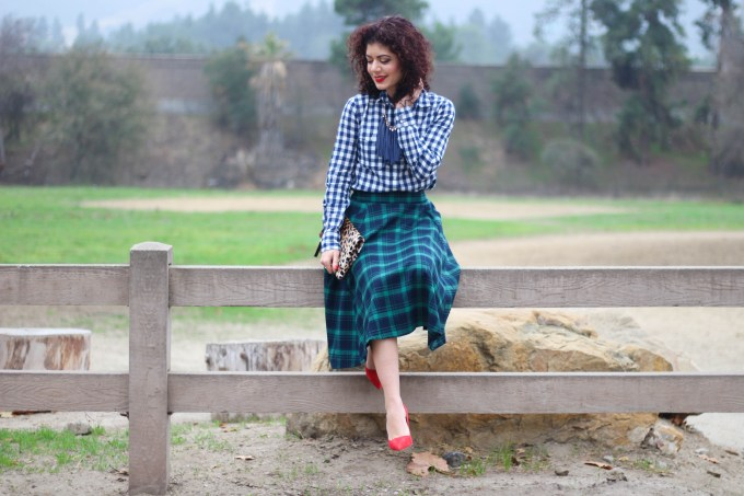 Polished whimsy pattern mixing in gingham shirt and green tartan skirt