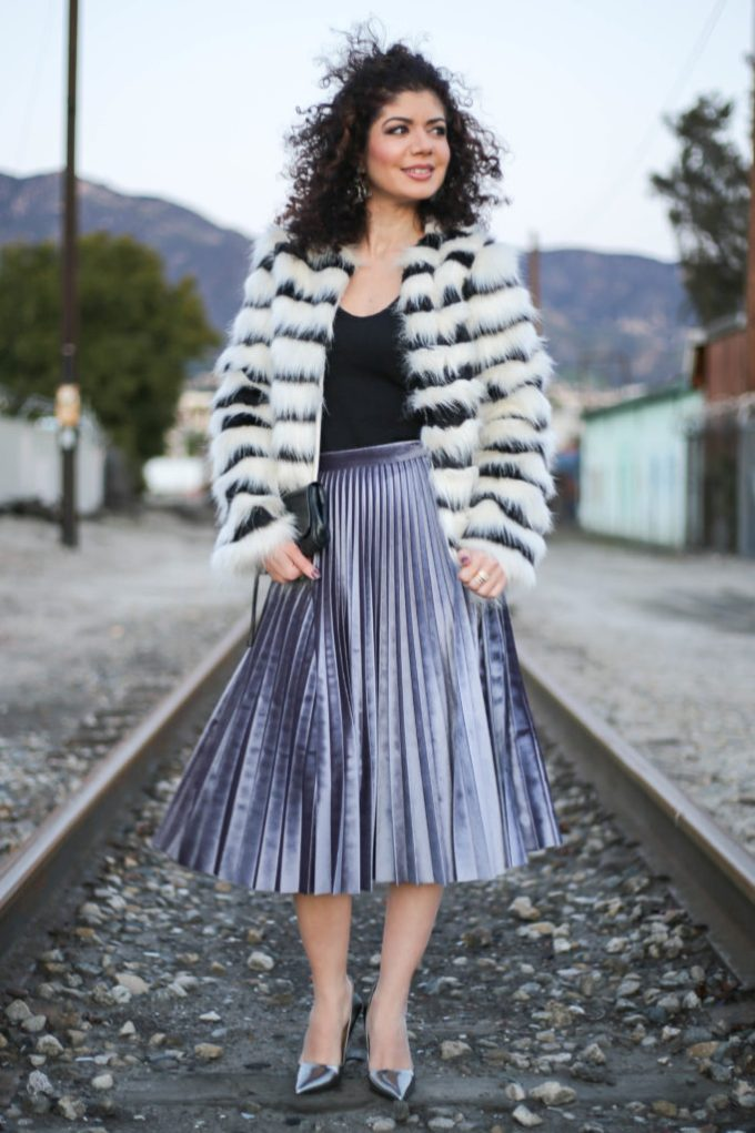 Polished whimsy in striped fur coat and pleated velvet skirt