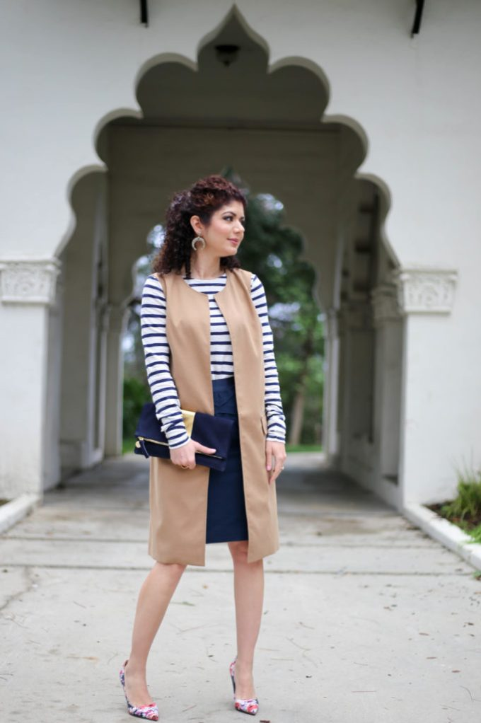Everyday style blogger polished whimsy wearing a navy striped top, navy pencil skirt, camel long vest and floral pumps for a spring ready work outfit.