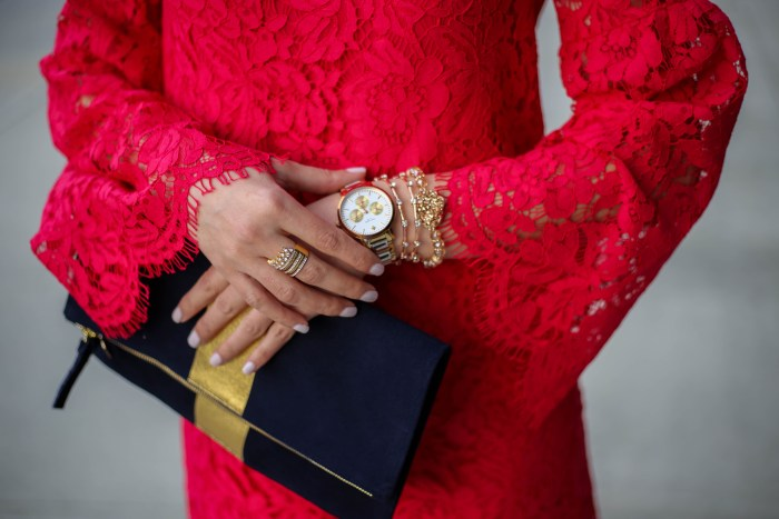 everyday style blogger polished whimsy wearing devlin pink lace bell sleeve dress with clare v blue and gold stripe clutch and rose gold watch and bracelets for spring transition outfit