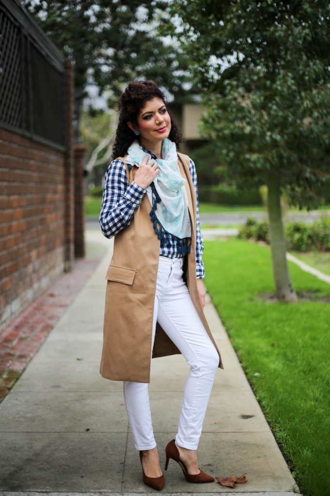 Everyday style blogger polished whimsy wearing white jeans, camel long vest, blue gingham shirt and floral embroidery scarf for a spring ready work outfit.