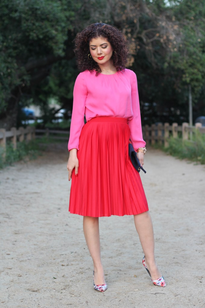 How to wear a pink and red outfit. Blogger Polished Whimsy shows how to put together a bold color blocking look with a red pleated skirt.