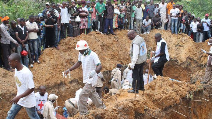 des-personnels-de-la-croix-rouge-pres-d-une-fosse-apres-le-massacre-de-22-personnes-par-des-rebelles-ougandais-le-20-octobre-2014-a-beni-dans-l-est-de-la-rdc_5166009
