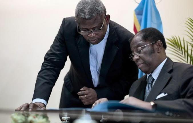 De gauche à droite, l'Abbé Donatien Shole et l'ancien ministre de Justice, Alexis Thambwe qui signe l'accord de la CENCO.