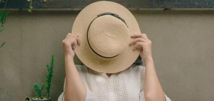 kobieta zasłaniająca się kapeluszem