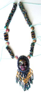 bead crochet pieces with polymer clay face and bead embroidery