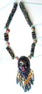 bead crochet with fringed polymer clay face