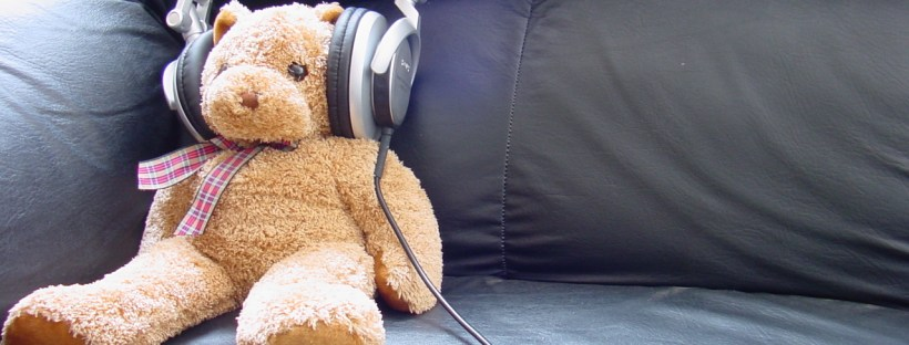 A teddy sitting on a sofa with headphones on. Possibly listening to Audible. Image by MediaLab on FreeImages.com.