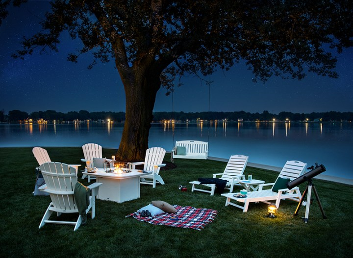 white adirondack and lounge chairs next to lake at night